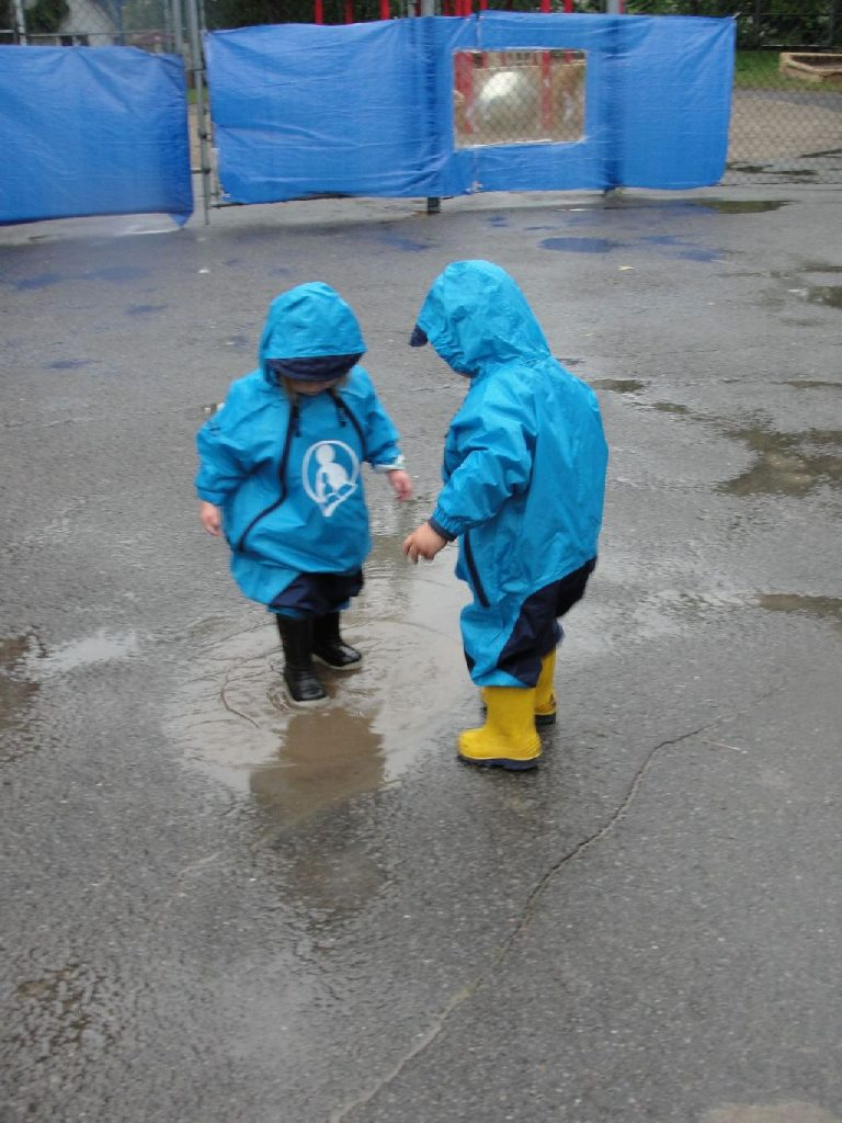 2 toddlers in rainsuits in a puddle