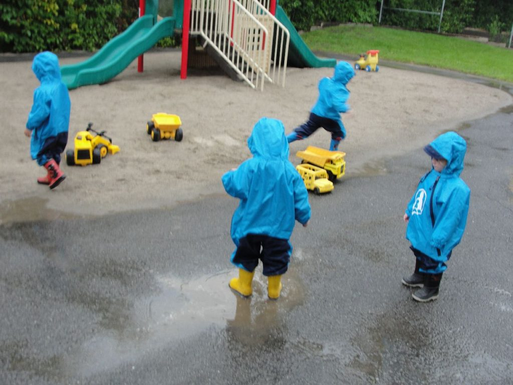 4 children in rainsuits playing in outdoor yard