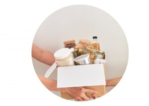 Box filled with food being handed from one person to another