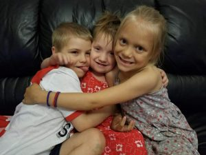 Photo of siblings; a little boy and two girls
