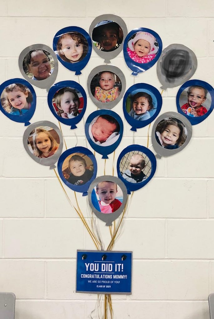 paper balloons with children's faces on them on a wall