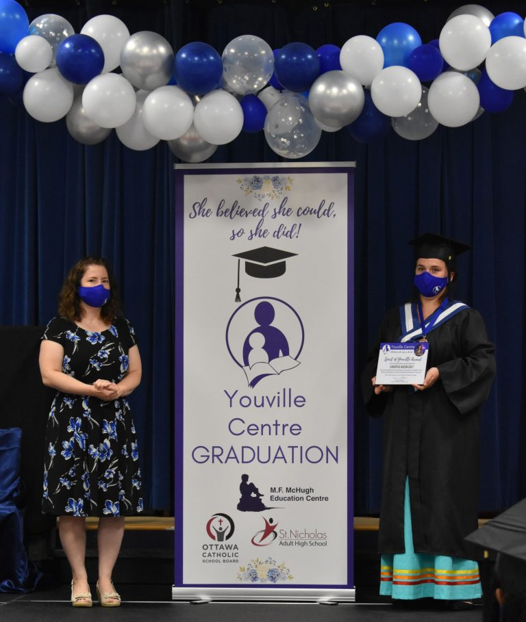 Young mother accepting Spirit of Youville award on stage