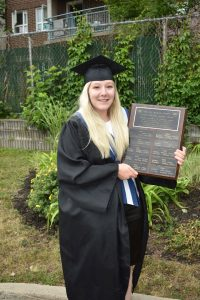 Young mother and graduate holding award